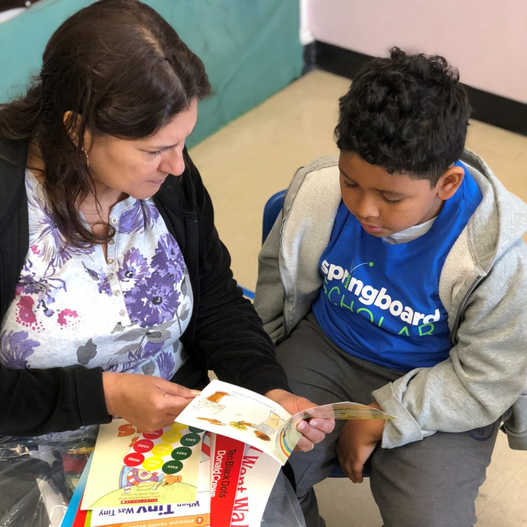 Parent holding a children's book for their child at a Springboard Collaborative family workshop