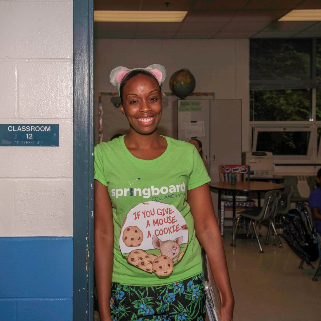 "Springboard Collaborative teacher wearing a ""If You Give A Mouse A Cookie"" sign in a classroom"