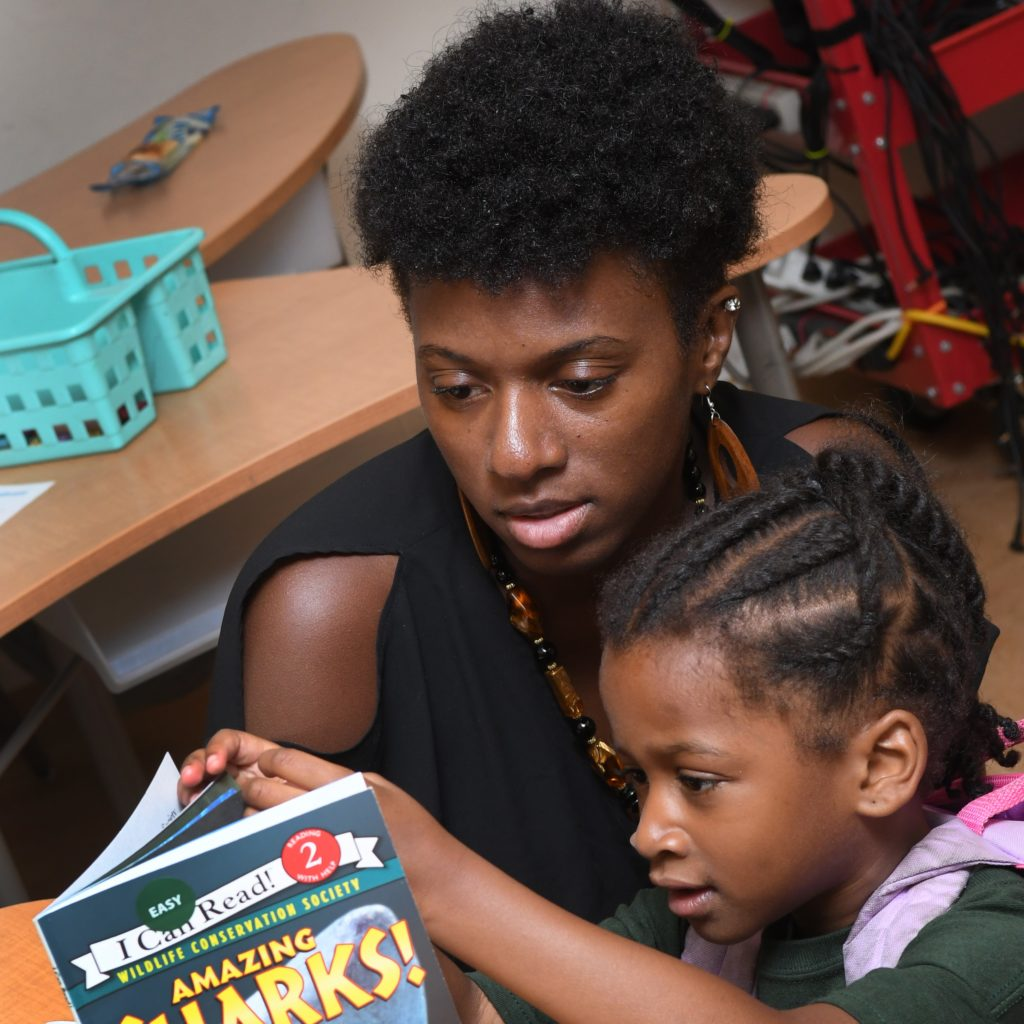 Family member reading a children's book out loud with their child at a Springboard Collaborative family workshop