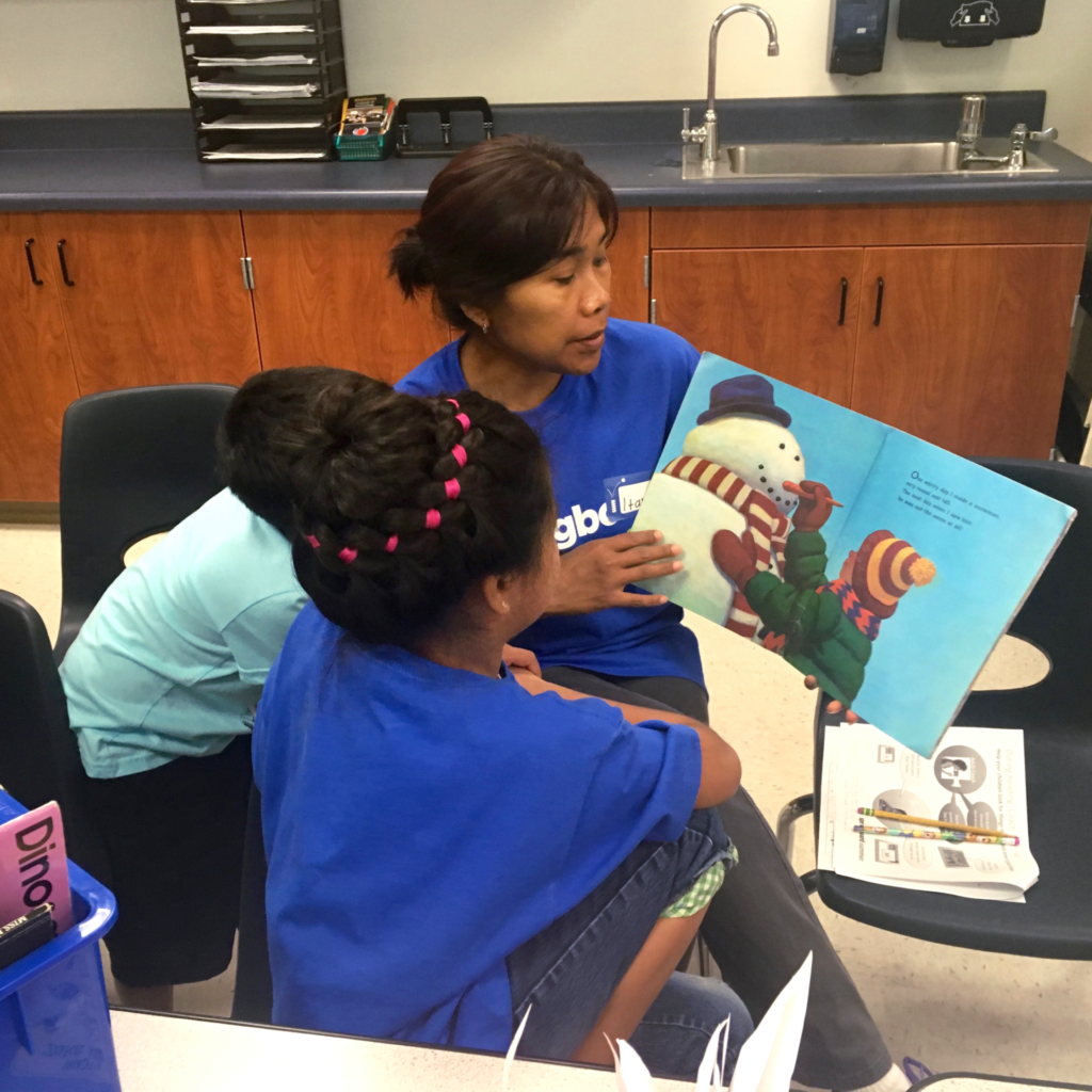 Family member reading a children's book to children at a Springboard Collaborative Summer family workshop
