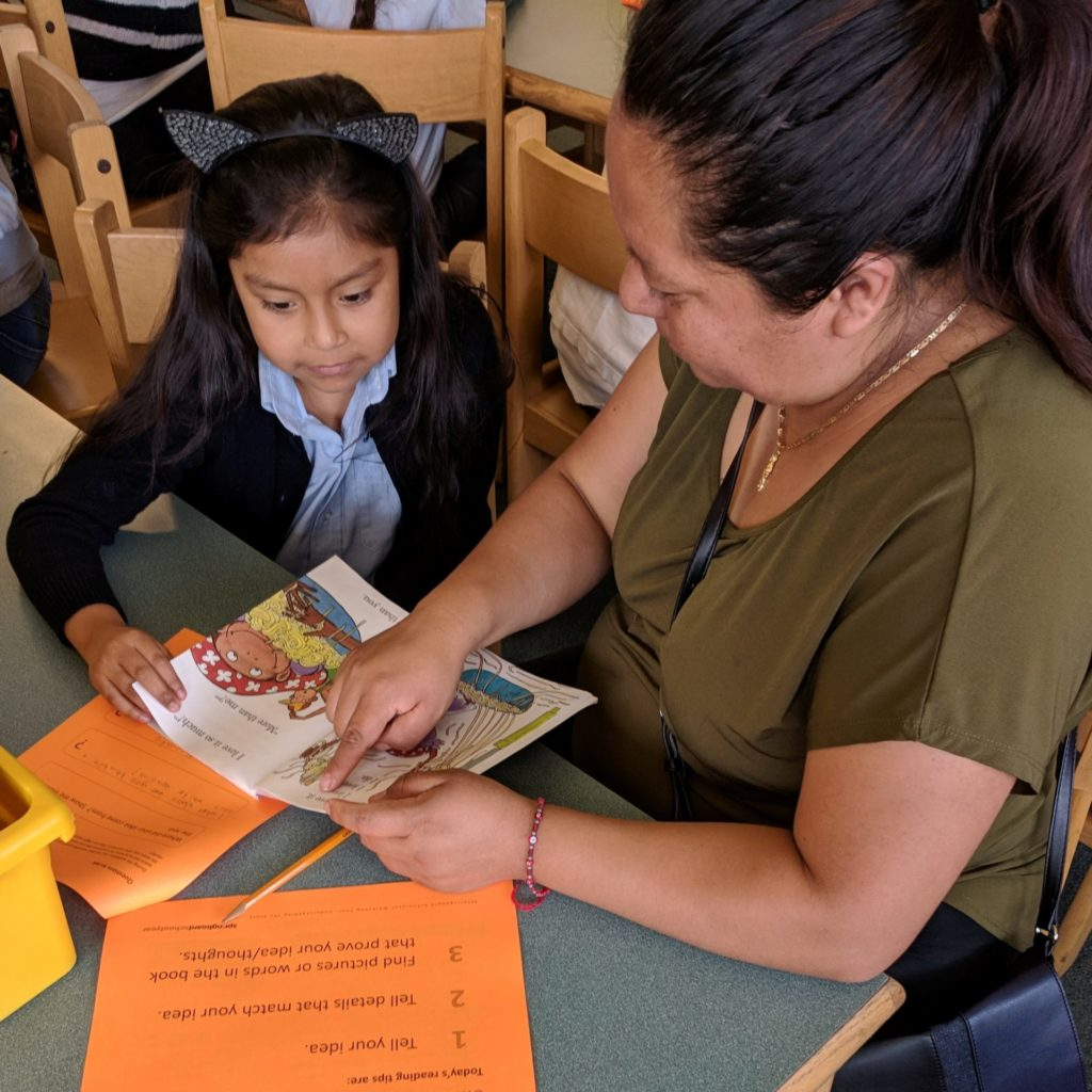 Child sitting with a family member that is pointing out a word in a children's book at a Springboard Collaborative family workshop