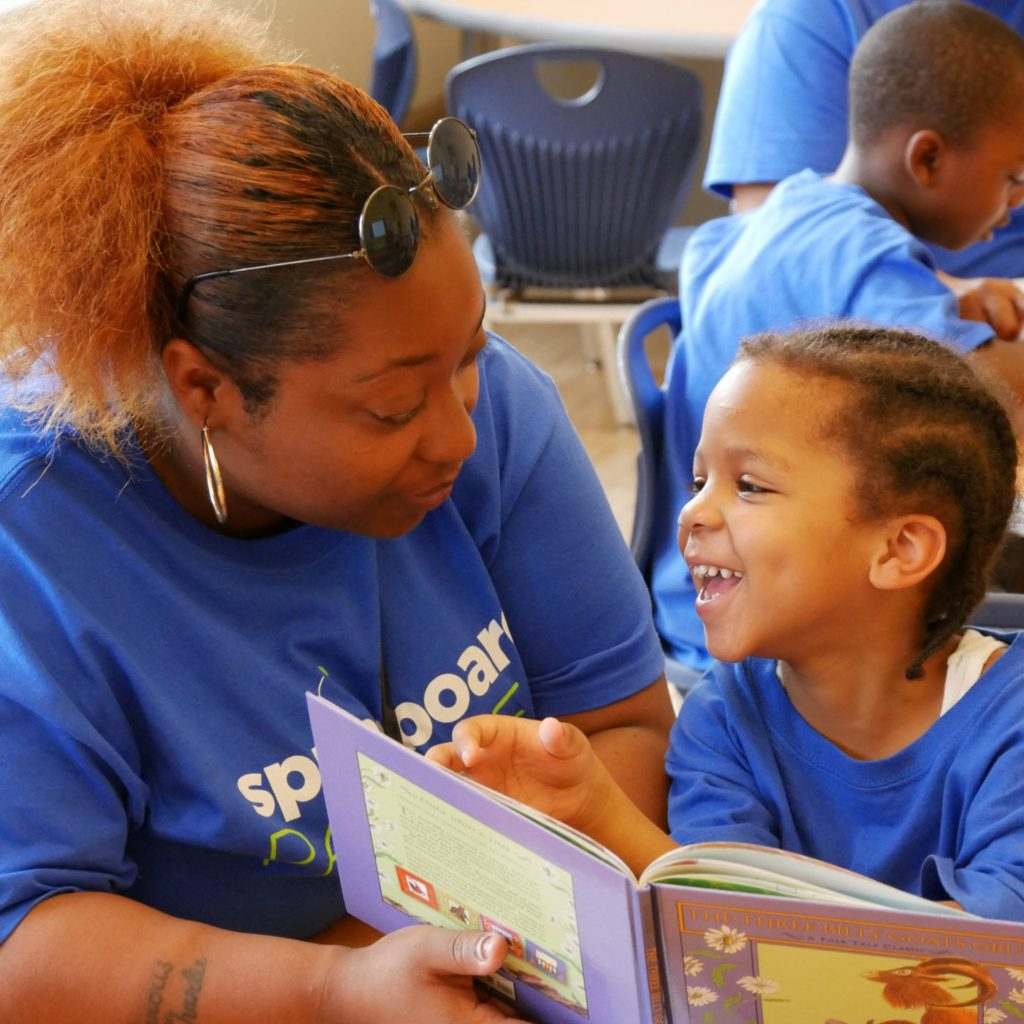 Family member reading a children's book to a child in a classroom at a Springboard Collaborative family workshop