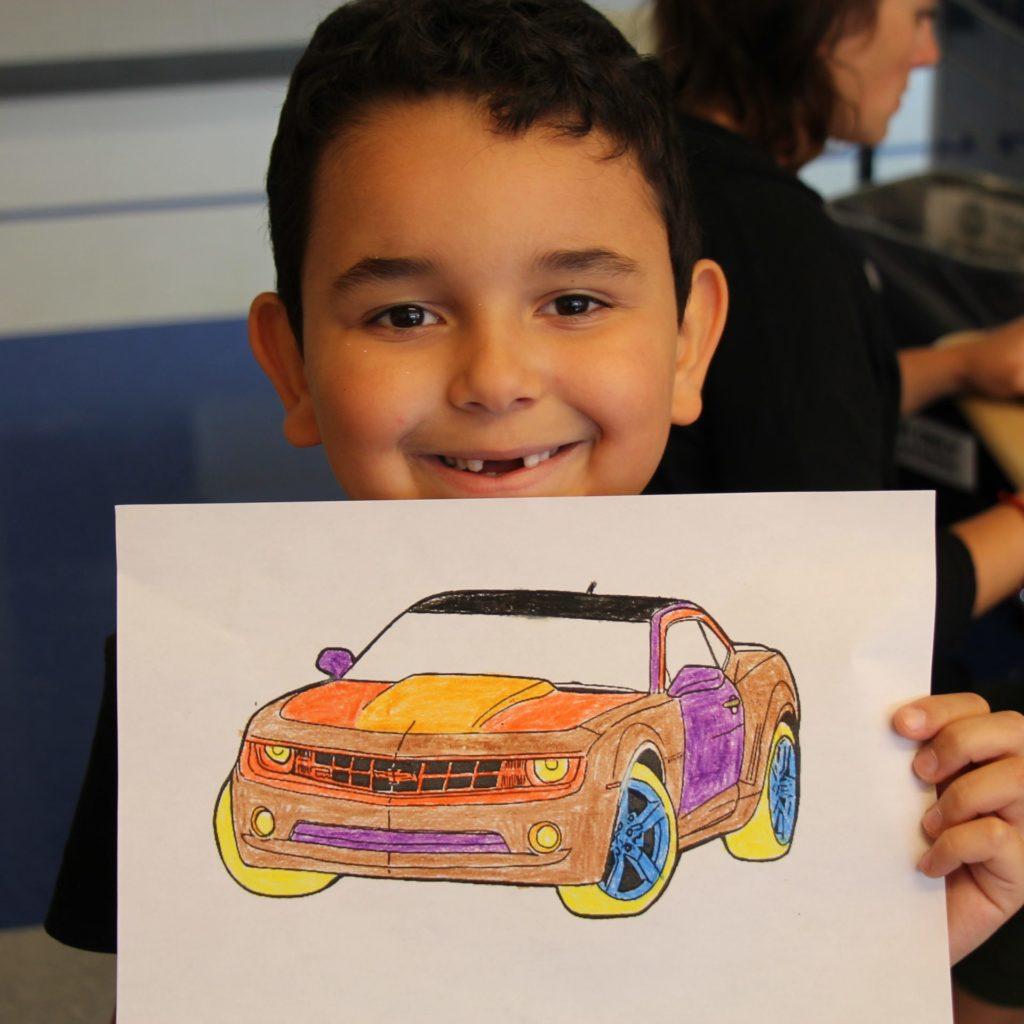Child holding up a colored-in race car coloring book picture and smiling